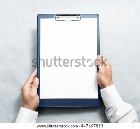 Hand holding blank clipboard with white a4 paper design mockup. Clear document holder mock up template hold arm. Clip board notepad surface display front. Checklist tablet plan file presentation. - stock photo