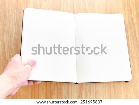 Hand holding blank open notebook lay it on wooden table,Template mock up for adding your text - stock photo