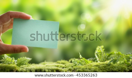 Hand holding blank paper card on nature background - stock photo