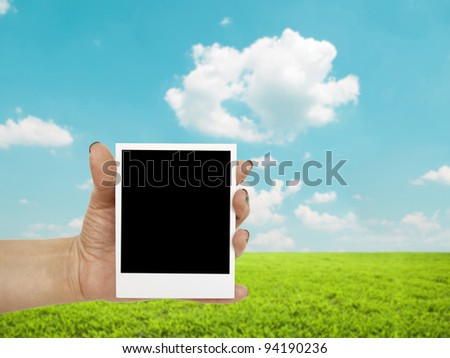 Hand holding blank photograph with landscape in background - stock photo