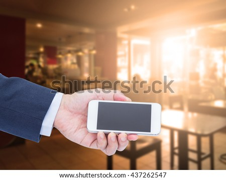 Hand holding blank screen mobile phone with blur coffee shop background - stock photo