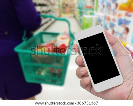 Hand holding blank screen mobile phone with blurred image of women carrying basket in supermarket - stock photo