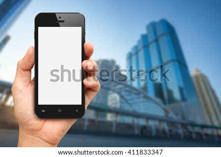 Hand holding blank screen smart phone with office building background - stock photo
