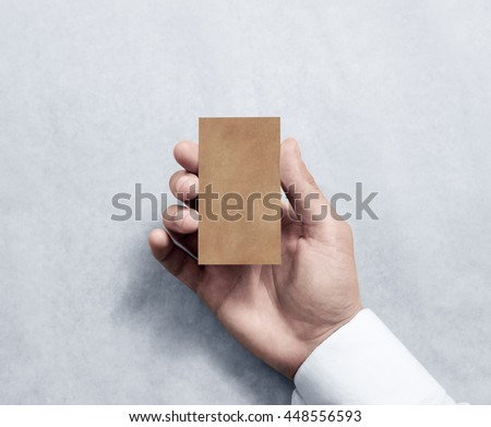 Hand holding blank vertical kraft business card design mockup. Clear calling card mock up template, craft paper. Pasteboard display front. Small offset texture card print. Business identity - stock photo