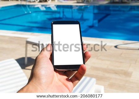 Hand holding blank, white, empty screen smart phone with copy space on poolside. - stock photo