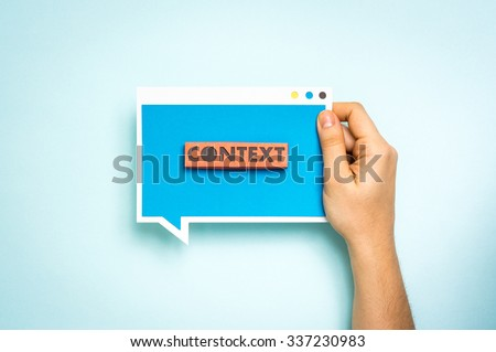 """Hand holding blue speech bubble with the text """"context"""". """"Context Marketing"""" concept. - stock photo"""