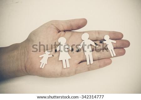 hand holding broken paper cut family - stock photo