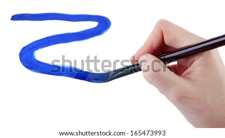 Hand holding brush with blue paint isolated on white - stock photo