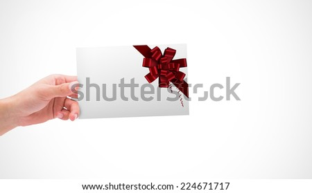 Hand holding card against red christmas bow and ribbon - stock photo