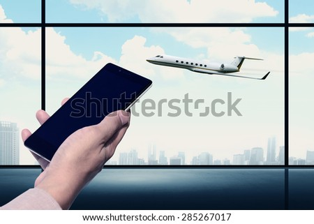 Hand holding cellphone with blank screen on the airport. You can put your design on the cellphone - stock photo