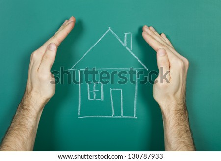 Hand holding chalk drawing house on blackboard - stock photo