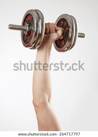 Hand holding chrome dumbbell on the white background. - stock photo