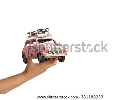 Hand holding classic mini model with bicycle, isolated on white background (travel concept) - stock photo