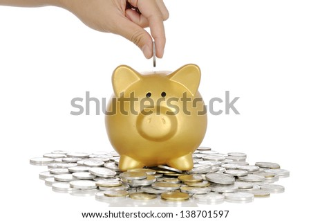 Hand holding coin into golden piggy bank with stack of coin - stock photo