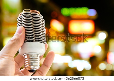 hand holding coin light bulb with defocused city night light background, energy concept - stock photo
