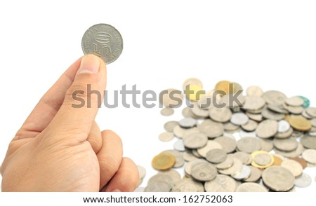 Hand holding coin over white background - stock photo