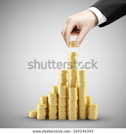hand holding coins and build coin city - stock photo