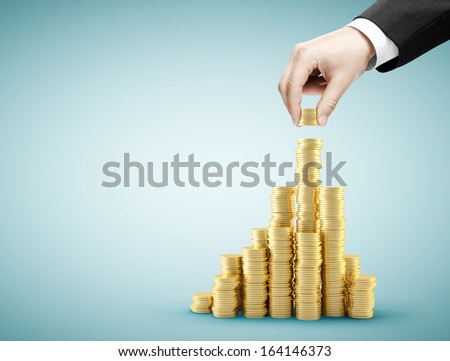 hand holding coins and build coin graph - stock photo
