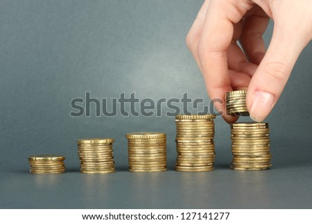 Hand holding coins on grey background - stock photo