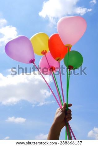 hand holding colorful balloon - stock photo