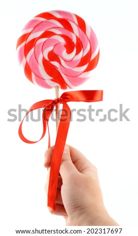 Hand holding colorful spiral lollipop isolated on white background - stock photo