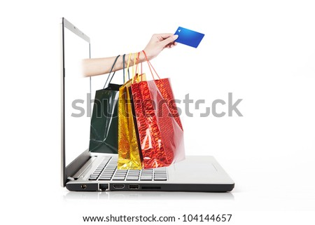 Hand holding credit card and shopping bag from laptop computer - stock photo