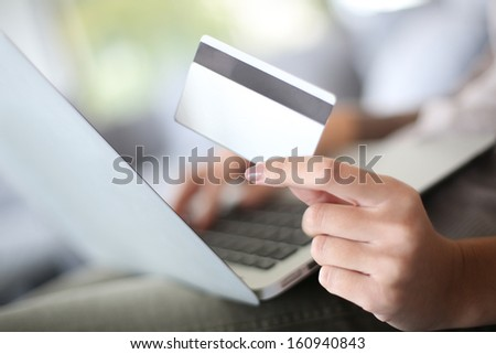 Hand holding credit card to buy online - stock photo