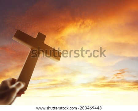 Hand holding cross in the sky - stock photo