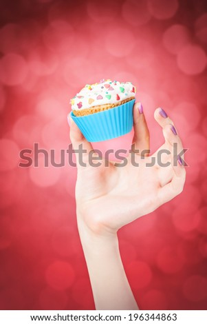 Hand holding cupcake on red bokeh background - stock photo