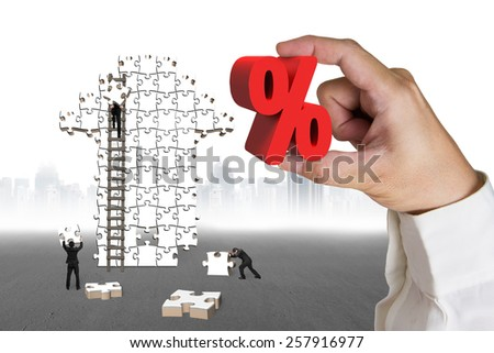Hand holding 3D red percentage sign with businessmen building arrow jigsaw puzzle and gray ground cityscape background - stock photo