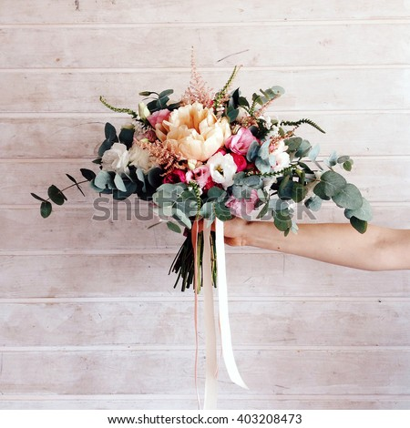 Hand holding delicate bouquet with ribbons, beautiful composition isolated on the wooden background. - stock photo