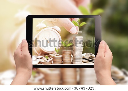 hand holding digital tablet with a picture of hand stacking coins with green plant ,Business Finance and Money concept,Save money for prepare in the future. - stock photo