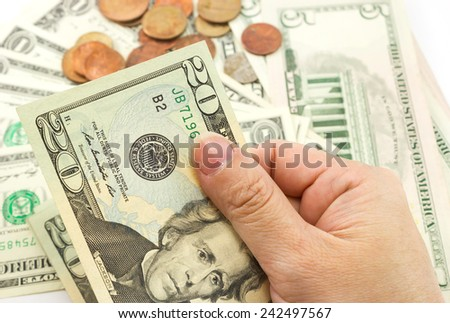Hand holding dollar bill with coins and dollar bills are background. - stock photo