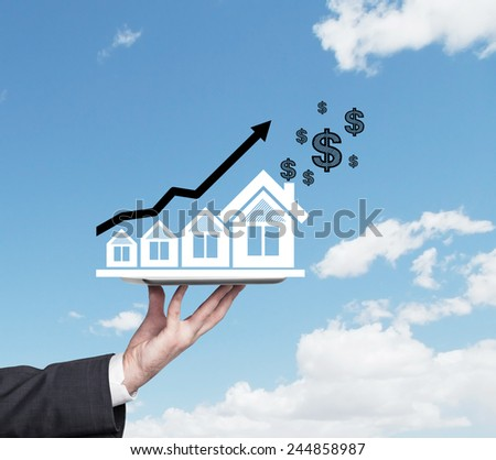 hand holding drawing house, blue arrow and dollars - stock photo