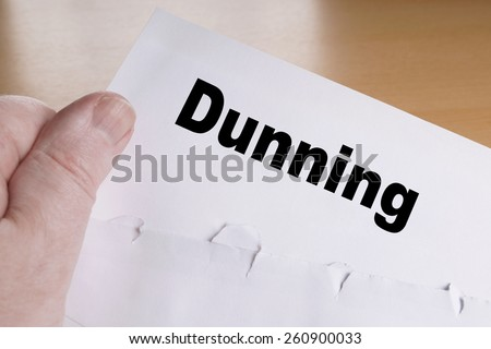 hand holding dunning letter with opened envelope - stock photo