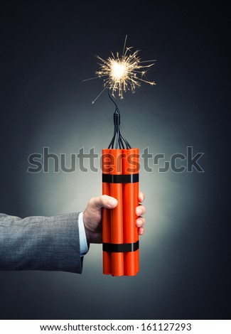 Hand holding dynamite with burning wick - stock photo