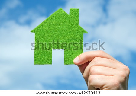 Hand holding eco house icon concept on the blue sky with clouds background - stock photo