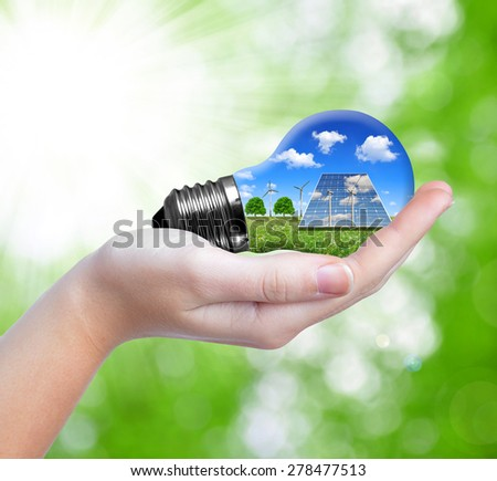 Hand holding eco light bulb on green background - stock photo