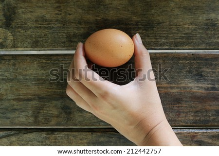Hand Holding Eggs on wooden table background - stock photo