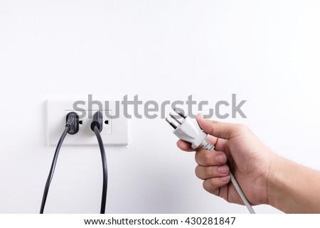 Hand holding electric plug isolated on white background - stock photo