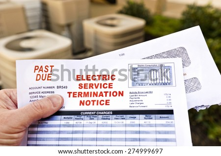 Hand Holding Electric Service Termination Notice In Front Of Air Conditioning Units - stock photo