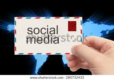 hand holding envelope with social media word on world background. - stock photo
