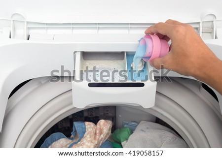 Hand holding fabric softener in washing machine. - stock photo