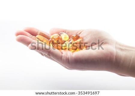 Hand holding fish oil capsules on white background, stock photo - stock photo