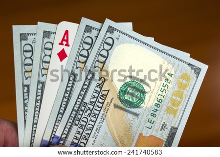 Hand holding four new one hundred dollar bills and an As of diamonds card, like if it was a poker hand. - stock photo