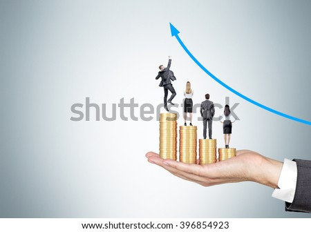 Hand holding four piles of coins of different size, businesspeople on them. Grey background, blue arrow up. Concept of career growth. - stock photo