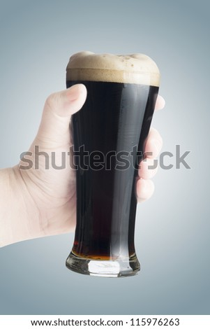 Hand holding fresh cold glass of dark beer - stock photo