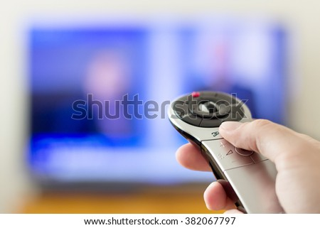 Hand holding futuristic remote control of a television - stock photo