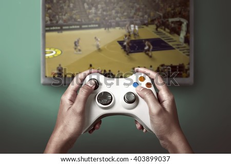 Hand holding game console controller playing sport game on the television - stock photo