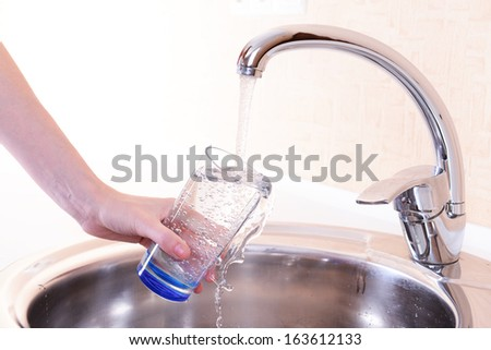 Hand holding  glass of water poured from  kitchen faucet - stock photo